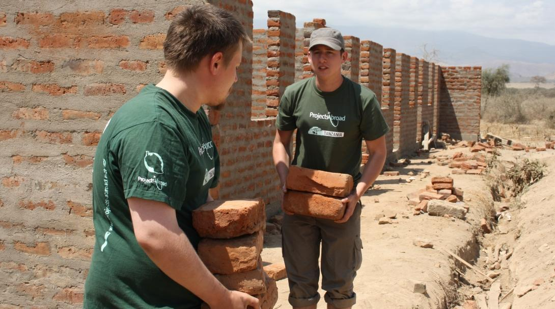 Two volunteers are seen carying bricks whilst on their building volunteer work in Tanzania with Projects Abroad